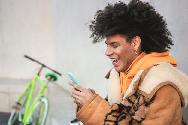 屋外でスマートフォンを使用している黒人のミレニアル世代のバイカー男-お気に入りに焦点を当てる