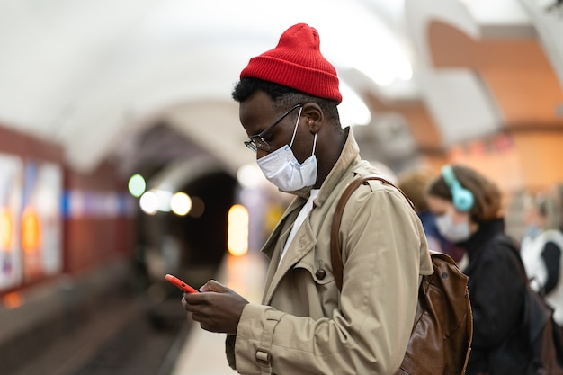 Black millennial man wear face mask, flu virus, waiting train at subway station, using smartphone