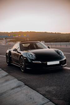 Black mini coupe on the road.