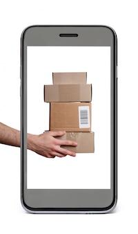 配送ボックスを保持している手で黒の携帯電話。白で隔離。