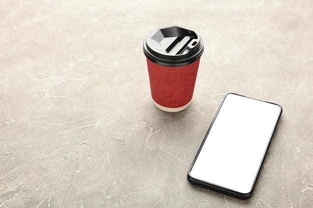 一杯のコーヒーと黒のモバイルスマートフォン