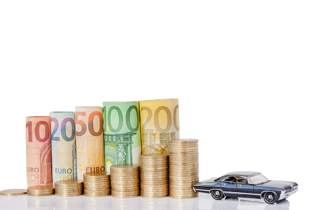 A black model of a car and ten, twenty, fifty, one hundred, two hundred and coins euro rolled bills banknotes on white surface. histogram from the euro. concept of currency growth, savings.
