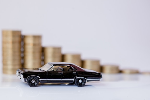 A black model of a car with coins in the form of a histogram