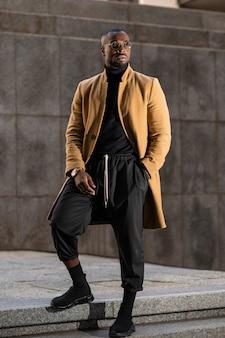 Черная модель позирует в элегантном стильном костюме. городской образ жизни