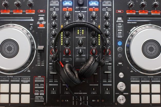 黒のモダンなオーディオコントローラーとプロ仕様のヘッドフォン。 dj楽器のセット。上面図