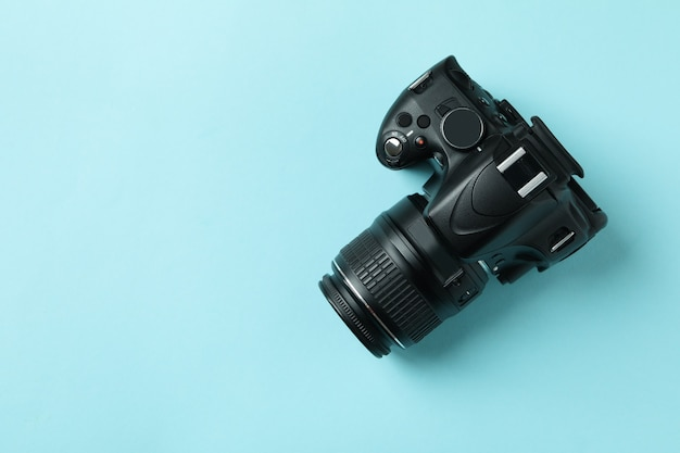 Black modern camera on blue background, space for text