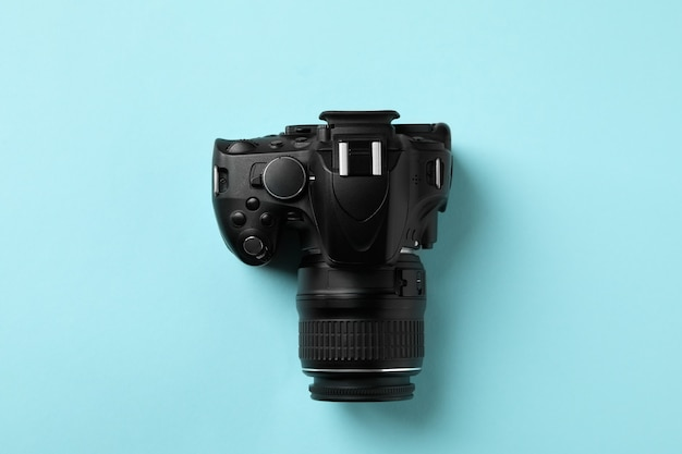 Black modern camera on blue background, top view