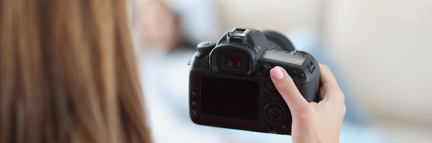 Black modern camera in female hand closeup