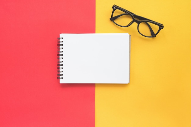 Black modern eye glasses and blank notebook on red and yellow background.