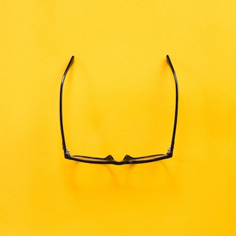 Black modern eye glasses on yellow.