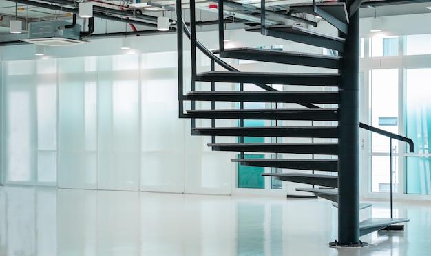 Black modern spiral stair in business office with windows, contemporary interior floor stairway design