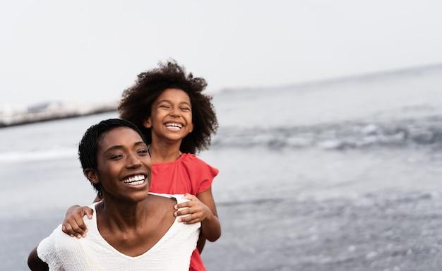 Черная мать и дочь бегают на пляже во время заката во время летних каникул - фокус на лице матери