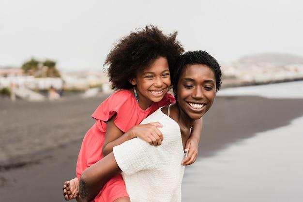 Черная мать и дочь бегают на пляже во время отпуска - фокус на лице мамы