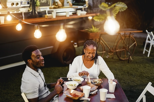 Black mother and son eating and drinking healthy food at food truck restaurant outdoor - focus on senior woman face