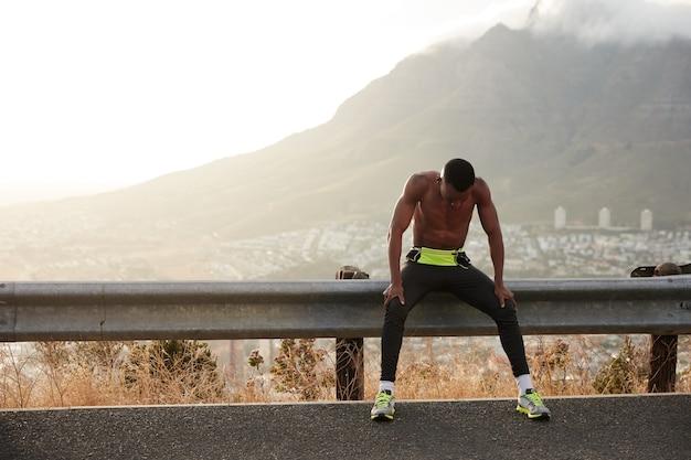 黒人のやる気のあるスポーツマンは、アクティブなフィットネストレーニングの後に疲れを感じ、自由なライフスタイルを楽しんで、朝のジョギングの後に休憩し、視線を保ち、短い髪、筋肉質のアスリートの体、外での運動