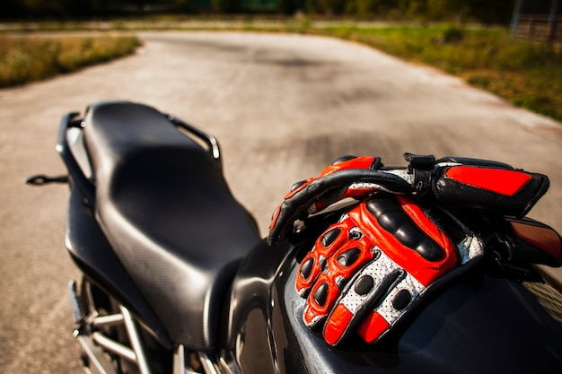 Black motorbike with riding red gloves