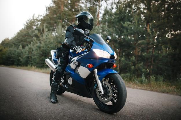 Черный водитель мотоцикла в шлеме и кожаном костюме