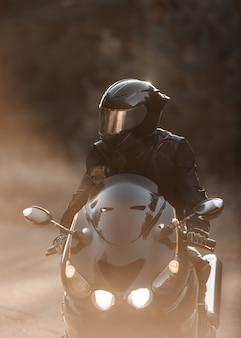 Черный водитель мотоцикла с включенными фарами в шлеме смотрит в сторону на дороге