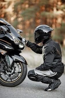 Черный мотоциклист в шлеме сидит возле спортивного мотоцикла и кладет на него руку