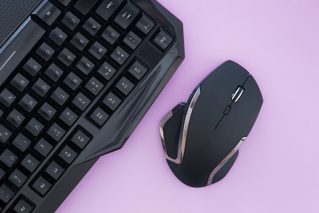 Black mouse and keyboard on a pink background, top view. workplace, mouse and keyboard flat lay