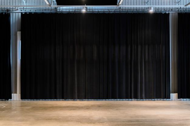 コンクリートの床の黒い映画館のカーテン。空のスペア。