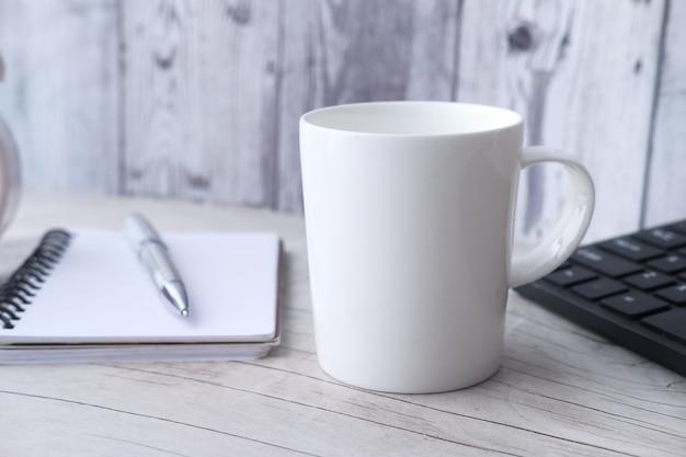 Макет черной кружки с клавиатурой, ноутбуками на столе.