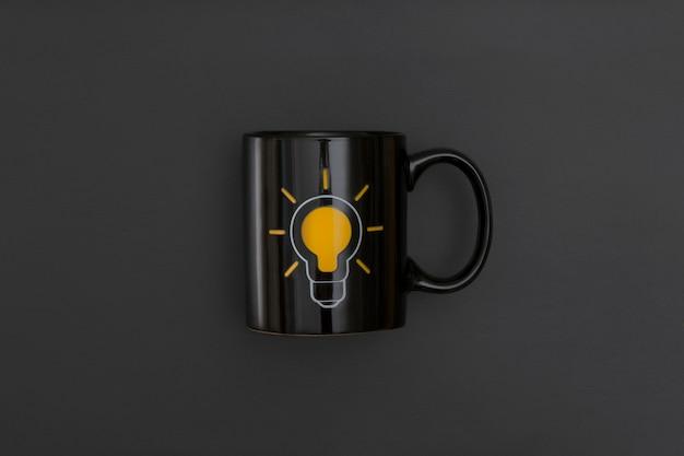 黒革の背景に黒のマグカップ。インスピレーションと創造的なアイデアのコンセプト。コピースペースのある上面図。フラットレイ構成。