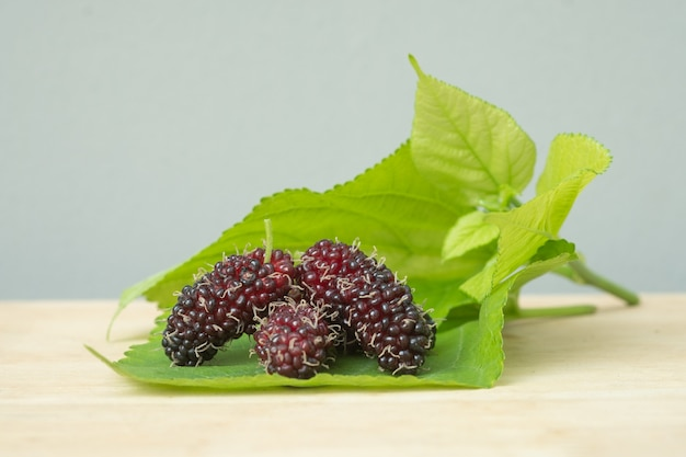 Black mulberries with leaf isolated on wooden table.