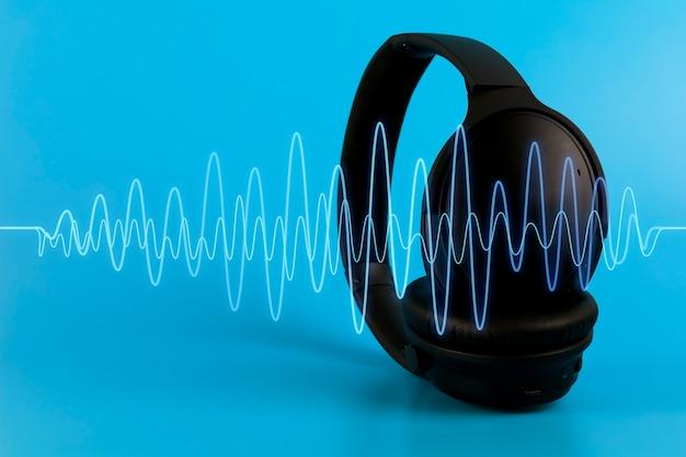 Черные музыкальные наушники с синей звуковой волной на синем фоне. мультимедийная концепция с копией пространства