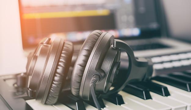 Black music studio headphone lying on working desktop