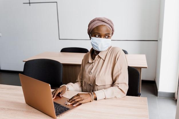 ラップトップと医療マスクの黒人イスラム教徒のビジネス女性。