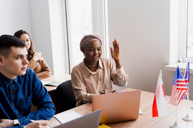Black muslim woman raise her hand and ask teacher the question. foreign school private study with a school woman. teacher explain grammar of native language using laptop. prepearing to exam with tutor.