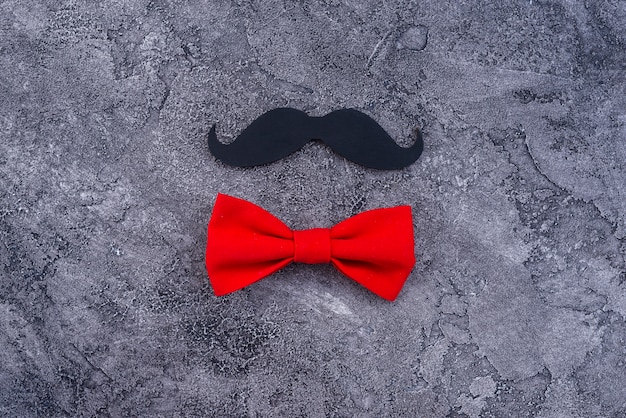 Black mustache and red bow tie