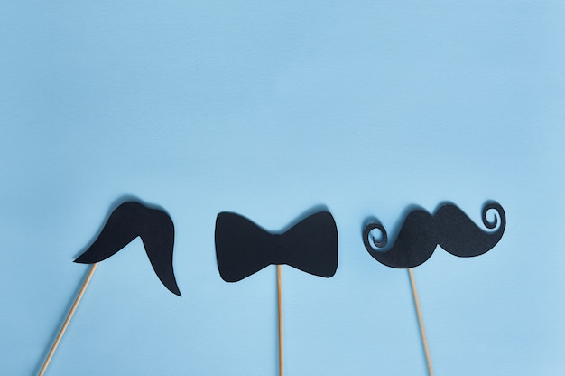 Black mustaches on blue paper background