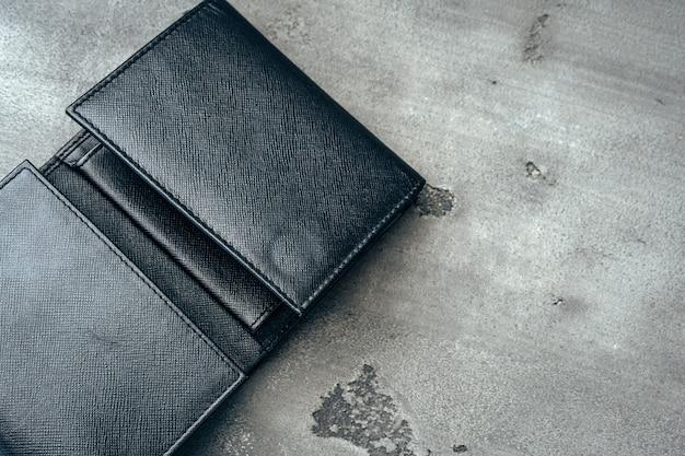 灰色のコンクリートの背景に黒の新しい革の財布