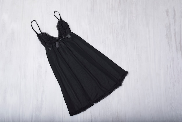 Black nightie on a wooden background. fashion concept