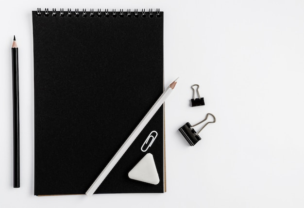 Black notebook blank mockup, pencils and stationery on white background.