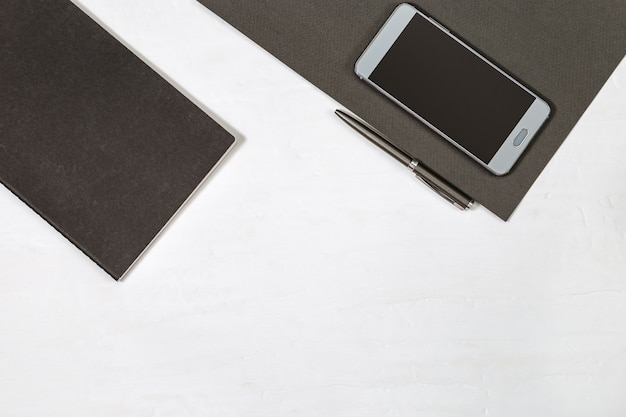 Black notebook, gray metallic pen, smartphone on table. flat lay concept for school or business. top view with copy space.
