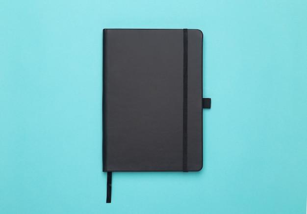 ブルーフラットレイアウトまたはトップビュー角度に分離された黒いノート。