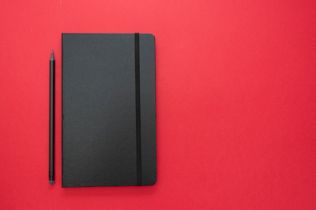 Black notebook on red background. top view of working table, work space. abstract business flat lay.