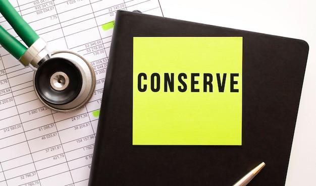 Conserveの刻印が入ったカラーステッカー付きの黒いノート。近くに電話内視鏡があります