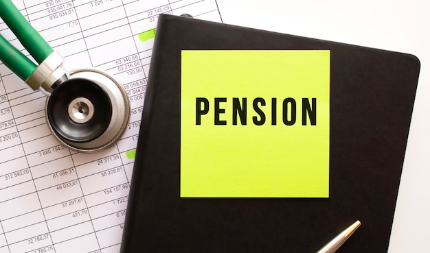 Черный блокнот с цветной наклейкой с надписью пенсия. рядом фонендоскоп. крупный план.