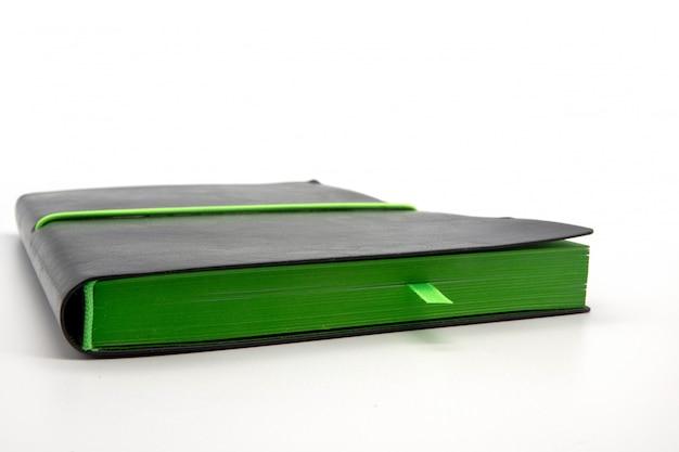 Черный блокнот с зеленым краем и закладкой на белом фоне