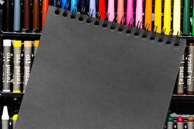 Black notepad and colourful markers and crayons