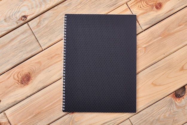 Black notepad on light wood. paper notebook with spiral. notice your goals and plans.
