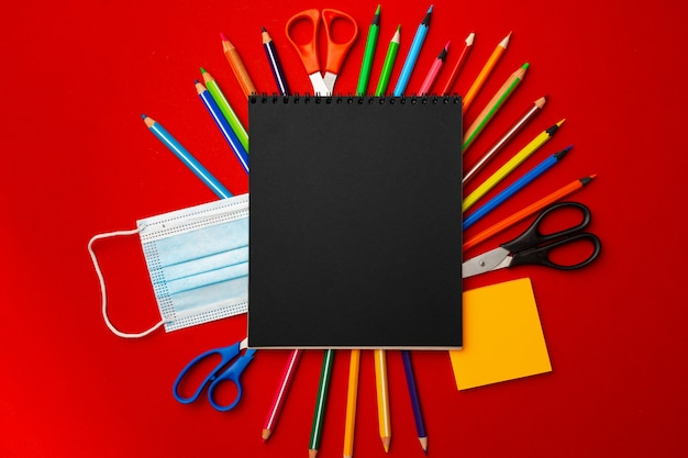 Black notepad page with stationery and medical mask on red