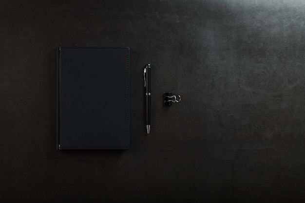 黒の背景に黒のペンで黒のメモ帳。上面図、ミニマルなコンセプト。フリースペース。