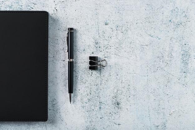 Черный блокнот с черной ручкой на сером фоне. вид сверху, минималистичная концепция. свободное место.
