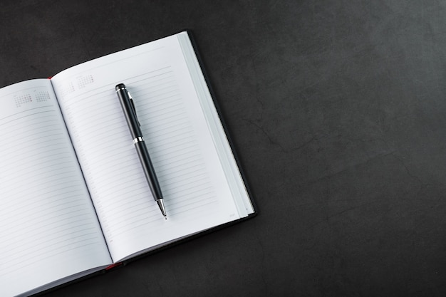 Black notepad with a black pen on a black background. top view, minimalistic concept. free space.