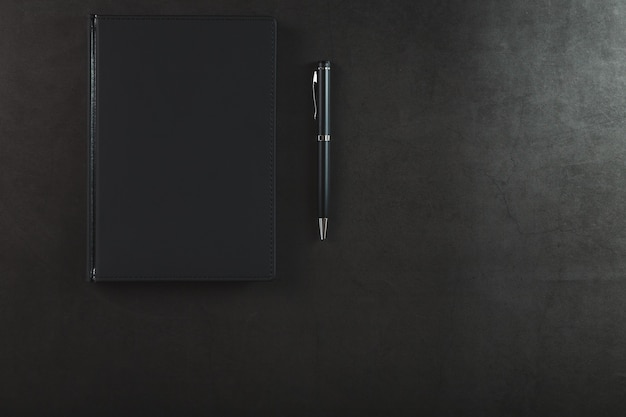Black notepad with a black pen on a black background.